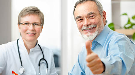 Female doctor and male patient (giving a thumbs-up gesture) looking at camera.