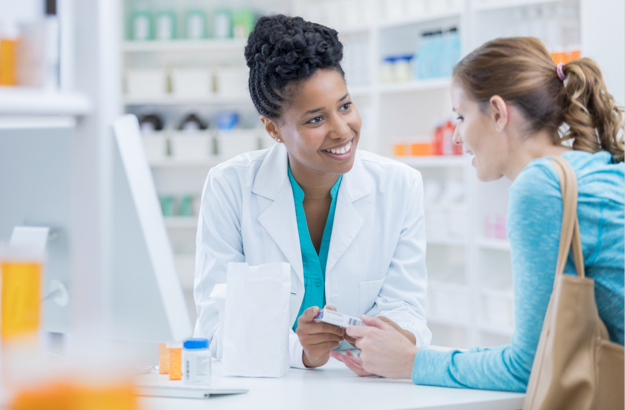 Young woman talking to a pharmacist at a pharmacy